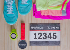 Top view of outfit for runner on wooden background. Bib number, finisher medal, gps watch, running shoes, shorts, shirt, and sport bra. Horizontal orientation Stock Photography
