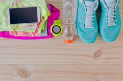 Top view of outfit for runner on wooden background. Bottle of water, gps watch, running shoes, running waist bag, shorts, shirt, and sport bra. Horizontal Royalty Free Stock Photography