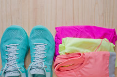 Top view of outfit for runner on wooden background. Running shoes,  shorts, shirt, and sport bra. Horizontal orientation Royalty Free Stock Photo