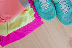 Top view of outfit for runner on wooden background. Running shoes,  shorts, shirt, and sport bra. Horizontal orientation Stock Photo
