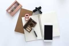 Top view over the beauty working desk with make up brush, eye shadows, notebooks, tapes and phone on the table. Copy space for tex. T. Flat lay on white Royalty Free Stock Photo