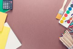 Top view over a brown background with school supplies on it. Notebooks, paints, brushes, coloured pencils and calculator from left. And right. Copy space for royalty free stock image