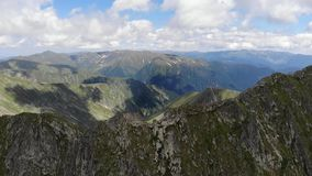 Top view over the Fagaras Mountains - Romania. Summer. Clear day with clouds. Clear Day. Cloudy. Mid day. Summer. Snow surfaces are visible. Rocky areas stock video
