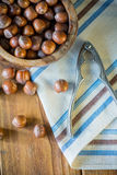 Top view over hazelnuts in bowl and nut cracker. On cloth Stock Image