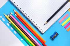 Top view over a notebooks, multicolored pencils, sharpener on a blue background. Back to school concept stock photos