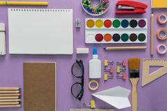 Top view over a pink background with school supplies on it. Back to school concept. Office supplies in a cartoon style stock video