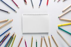 Top view over a school supplies as coloured pencils placed in a circle on a white background with blank work book in the middle of. It. Back to school concept stock photo