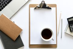 Top view over the working desk with notebooks, calculator, cup of coffee, pen, pencil and laptop. Copy space for text. Flat lay of. A workplace on white royalty free stock photo