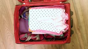 Suitcase with summer clothing. Top view - packing suitcase for a journey - time lapse. Girl dreams about travell. Summer clothing and diving mask with snorkel stock video footage