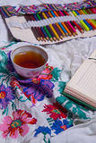 Top view of paint, a blank sheet of paper, cup of tea, markers. Stock Image