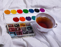 Top view of paint, a blank sheet of paper, cup of tea, markers. Stock Photo
