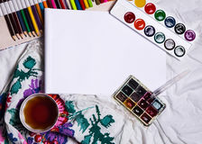 Top view of paint, a blank sheet of paper, cup of tea, markers. Top view of paint, a blank sheet of paper, cup of tea, markers , Workplace concept Royalty Free Stock Images