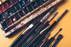 Paint brushes and watercolour paints at designer workplace Stock Images