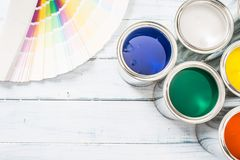 Top of view paint cans brushes and color palette on table.  royalty free stock photography