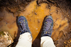 Top view of pair of boots in the middle of the mud. Royalty Free Stock Images