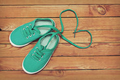 Top view of a pair of shoes with laces making heart shape on woo Royalty Free Stock Photography