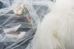 Top view of pair of shoes, wedding dress and bouquet on wooden dark. Blue tabletop stock photo