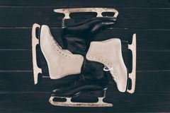 Pairs of white and black skates on wooden surface. Top view of pairs of white and black skates on wooden surface Stock Photo