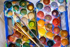 Top view of palette of paints and brushes in the process of work stock image