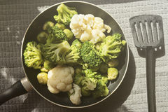Top view of the pan with fresh defrosted vegetables: cauliflower, broccoli, brussels sprouts. And kitchen spatula Stock Photos