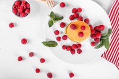 Top view of pancakes with raspberries on white wood background stock image