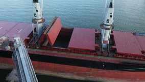 Top view panorama of opening cargo ship holds at silo terminal in seaport. Cereals bulk transshipment to vessel. Transrportation of agricultural products on stock video footage