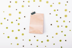 Top view of a paper bag with a gift and pattern of flowers. On a white background Royalty Free Stock Photo