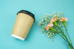 Paper coffee to go cup and flwers on blue background. Top view paper coffee to go cup  and flwers  on blue  background stock photo