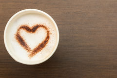 Top view of paper cup of coffee with heart symbol. On wooden table Stock Photography