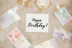 Top view of paper with happy birthday lettering surrounded with greeting cards. On concrete surface royalty free stock photos