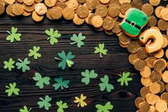 Top view of paper shamrock and golden coins on wooden table, st patricks day concept stock photography
