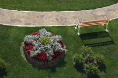 Top view on a park path. View from a terrace hotel on a park path,   bench, flowerbed and green lawn Royalty Free Stock Photos