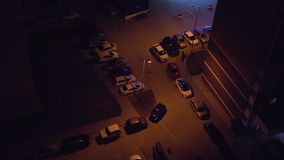 Top view of the parking lot from the roof of a skyscraper at night. Parking by various vehicles in the dark. Top view of the parking lot from the roof of a stock video