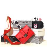 Top view party outfit composition: trendy female accessories red shoes, handbag clutch sunglasses, cosmetics, makeup, alarm clock royalty free stock photography