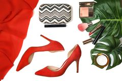 Top view party outfit red shoes, accessories makeup cosmetics, clutch, tropical monstera leaves on white background isolated. royalty free stock photography