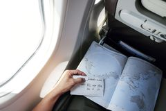 Passenger holding boarding pass in airplane Stock Images
