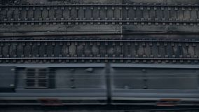 Top view on passing trains. Top view on fast electric modern train is going from right to left on railroad tracks in industrial district of town at gloomy rainy stock video