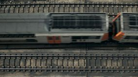 Top view on passing trains. Top view on large distance train with double deck cars is pasing by at sunny day on open railroad tracks in industrial district of stock video footage