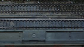 Top view on passing trains. Top view on fast electric modern train is going from left to right on railroad tracks in industrial district of town at gloomy rainy stock video