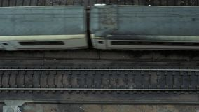 Top view on passing trains. Top view on open railroad or subway tracks in urban industrial district and metro train passing from left to right at rainy weather stock video