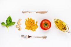 Top view of pasta ingredients and cutlery over white background - raw fusilli, fresh basil, garlic cloves, olive oil and ripe toma. Toe. Italian food minimal Stock Image