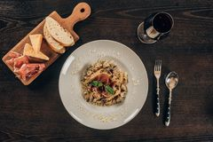 Top view of pasta with meat and glass of red wine. On table stock photos