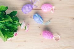 Top view of pink and blue checkered Easter eggs decorations and white and pink daisies on pale wooden background stock images