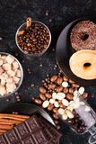 Top view of peanuts in chocolate, spilled on the dark board, next to chocolate tablets, donuts, brown sugar and coffee. Beans. Studio photo Stock Photos