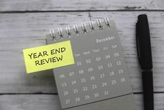 Top view of pen ,calendar and sticky note written with Year End Review on white wooden background