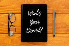 Top view of pen,eyeglasses,and book written with question What's Your Brand? on wooden background. Business concept. royalty free stock photography