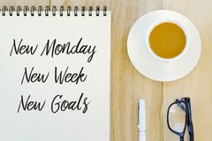 Top view of pen,glasses,a cup of coffee and notebook written with New Monday,New Week,New Goals. royalty free stock images