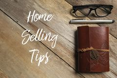 Top view of pen,glasses and notebook on wooden background written with Home Selling Tips. royalty free stock images