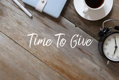 Top view of pen,notebook,coffee and clock on wooden background written with Time To Give. Take giving money watch help reminder deadline charity share donation stock photography