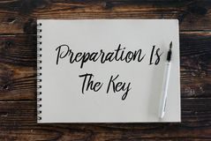 Top view of pen and notebook written with Preparation Is The Key stock images